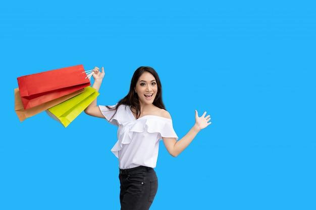 Schöne asiatische junge frau mit einkaufstüten mit lächeln beim stehen im bekleidungsgeschäft. glück, konsum, verkauf und menschenkonzept Premium Fotos