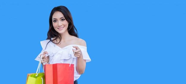Schöne asiatische junge frau steht und hält einkaufstaschen. sie lächelt glück im einkaufszentrum auf blauem hintergrund Premium Fotos