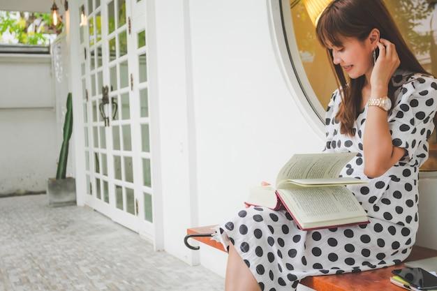 Schöne asiatische junge frauen, die das lesebuch im freien sitzen Premium Fotos