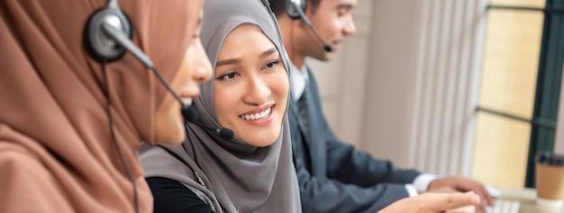 Schöne asiatische moslemische frau, die im kundenkontaktcenter mit team, panoramische fahne arbeitet Premium Fotos