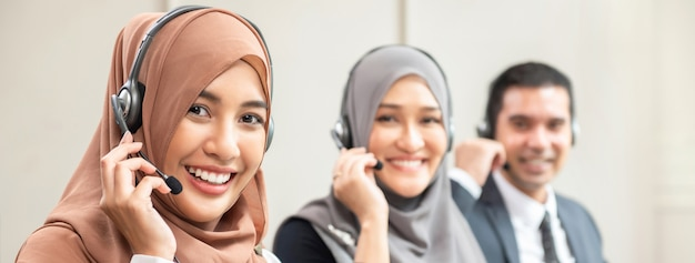 Schöne asiatische moslemische frauen, die im kundenkontaktcenter mit team, panoramische fahne arbeiten Premium Fotos