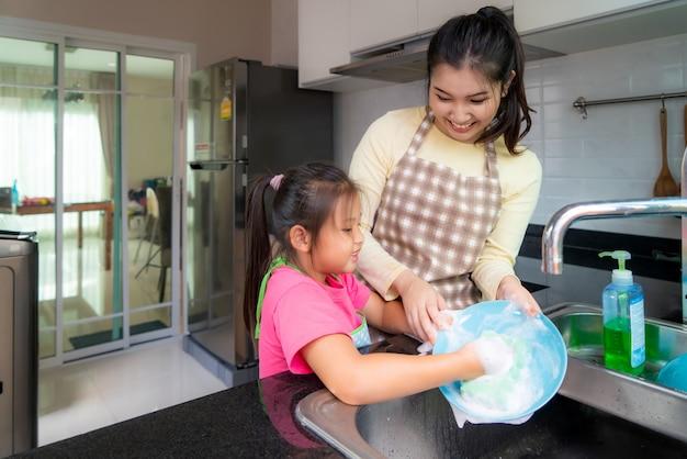 Schöne asiatische mutter und tochter, die spaß haben, während geschirr zusammen mit waschmittel auf spüle in der küche zu hause spülen. Premium Fotos