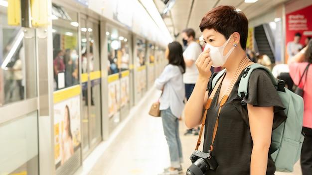 Schöne asiatische reisende mittleren alters decken mund und husten ab, tragen medizinische gesichtsmaske, um vor infektion mit viren, pandemie, ausbruch und krankheitsepidemie in überfüllten u-bahn zu schützen Premium Fotos
