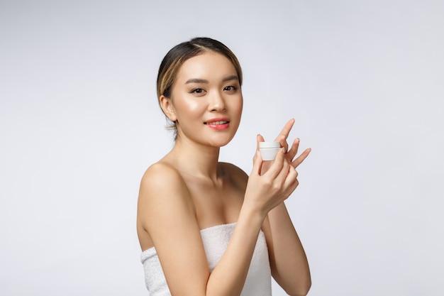 Schöne asien-frau, die das produkt lokalisiert auf weißem hintergrund darstellt. Premium Fotos