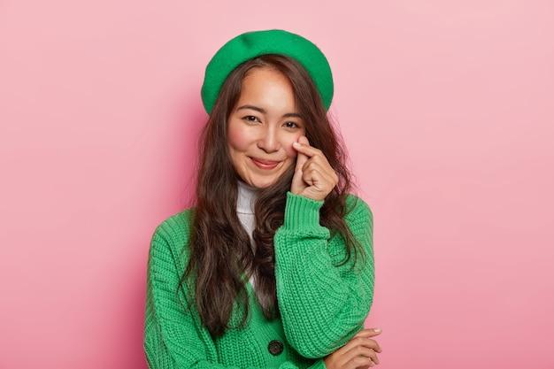 Schöne attraktive brünette frau macht koreanisch wie geste, formt kleines herz mit den fingern, hat langes dunkles glattes haar, trägt grüne baskenmütze und pullover auf knöpfen Kostenlose Fotos