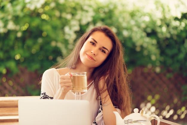 Schöne attraktive frau am café mit einem laptop, der eine kaffeepause hat Premium Fotos