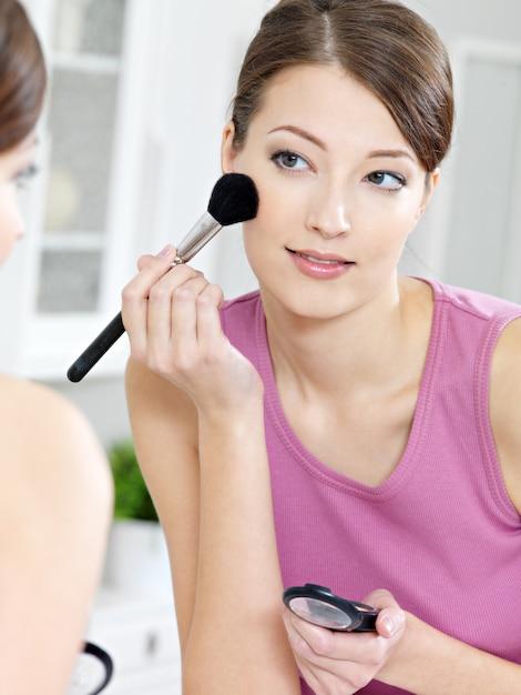 Schöne attraktive frau, die lidschatten mit pinsel anwendet, der in den spiegel schaut Kostenlose Fotos