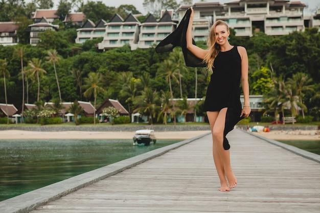 Schöne attraktive frau gekleidet im schwarzen kleid, das auf pier im luxusresorthotel, sommerferien, tropischer strand aufwirft Kostenlose Fotos
