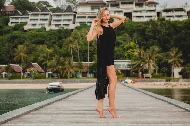 Schöne attraktive frau gekleidet in romantisches schwarzes kleid, das auf pier im luxusresorthotel aufwirft, Kostenlose Fotos