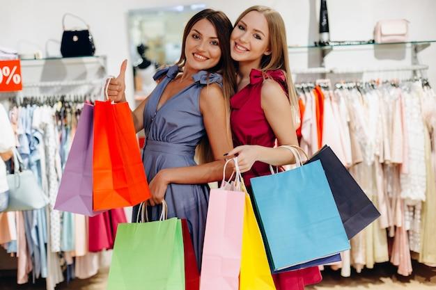 Schöne, attraktive freundinnen mit bunten taschen im showroom Premium Fotos