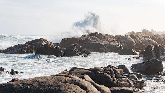 Schöne aufnahme der wellen des stürmischen ozeans, die die steine am ufer erreichen Kostenlose Fotos