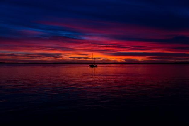 Schöne aufnahme des sonnenuntergangs am meer mit einem boot in der mitte Kostenlose Fotos