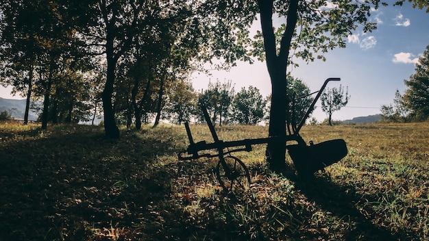 Schöne aufnahme einer silhouette einer konstruktion auf rädern, die neben einem baum in einem ländlichen feld geparkt wird Kostenlose Fotos