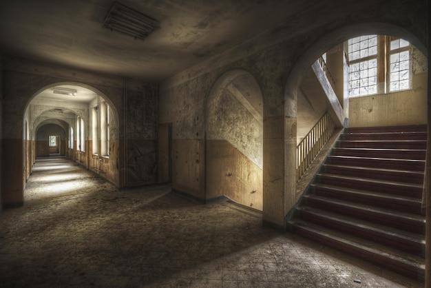 Schöne aufnahme eines flurs mit treppen und fenstern in einem alten gebäude Kostenlose Fotos