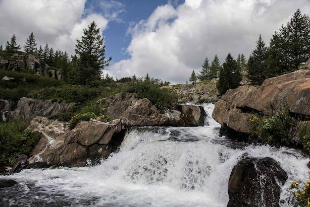 Schöne aufnahme eines kleinen wasserfalls mit felsformationen und bäumen um ihn herum an einem wolkigen tag Kostenlose Fotos