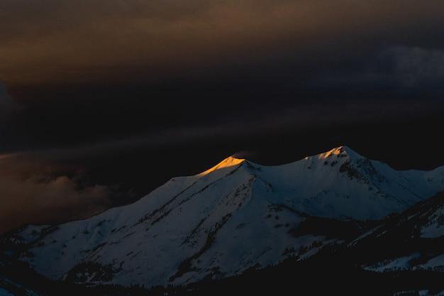Schöne aufnahme eines mit schnee bedeckten berges während der späten nacht Kostenlose Fotos