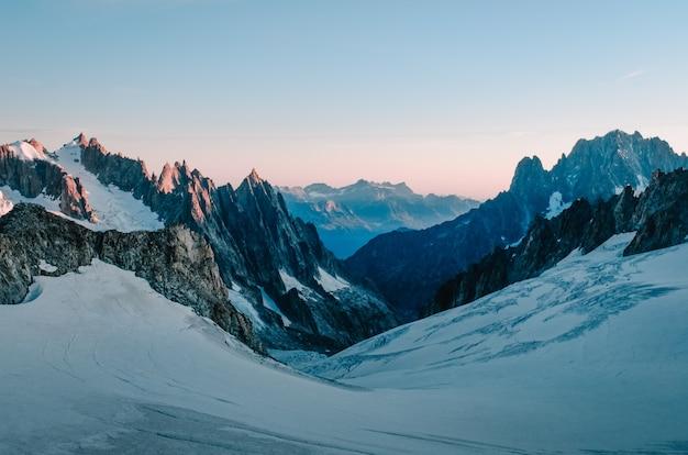 Schöne aufnahme eines schneebedeckten hügels, umgeben von bergen mit dem hellrosa himmel Kostenlose Fotos