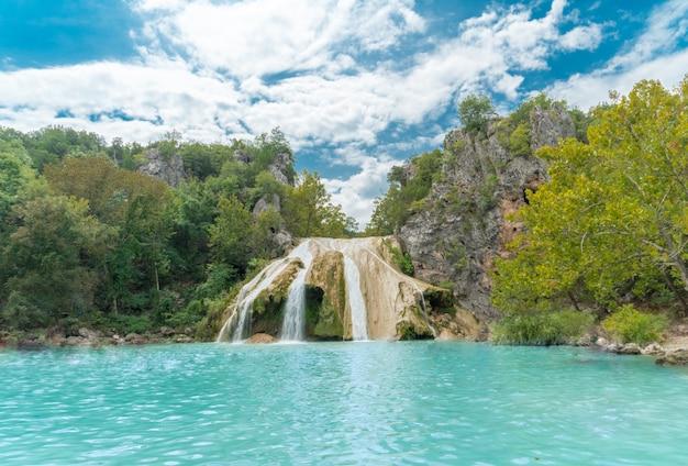 Schöne aufnahme eines sees mit dünnen wasserfällen, umgeben von grün und bergen Kostenlose Fotos