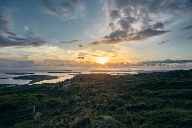 Schöne aufnahme eines sonnenuntergangs von sky road, clifden in irland mit grünen feldern und ozean Kostenlose Fotos