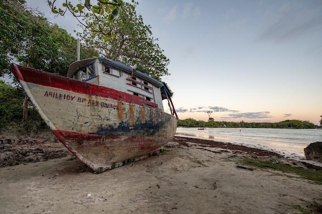 Schöne aufnahme eines verlassenen bootes an der küste Kostenlose Fotos