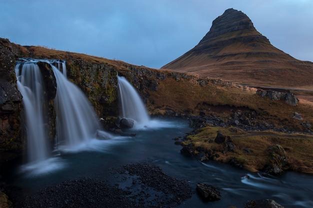 Schöne aufnahme von großen wasserfällen und einem berg mit einem blauen himmel Kostenlose Fotos