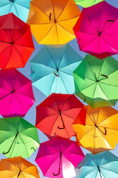 Schöne aufnahme von mehrfarbigen schwimmenden regenschirmen gegen den blauen himmel Kostenlose Fotos