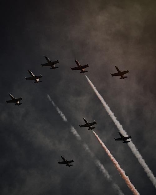 Schöne aufnahme von vielen flugzeugen im grauen himmel, die operationen und pirouetten ausführen Kostenlose Fotos