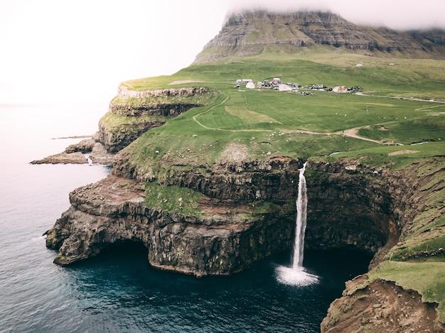 Schöne aussicht auf den wasserfall gasadalur und die färöer in dänemark Kostenlose Fotos