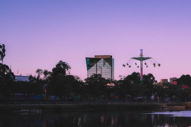 Schöne aussicht auf ein hohes glasgeschäftsgebäude mit hohen schaukeln an der seite Kostenlose Fotos
