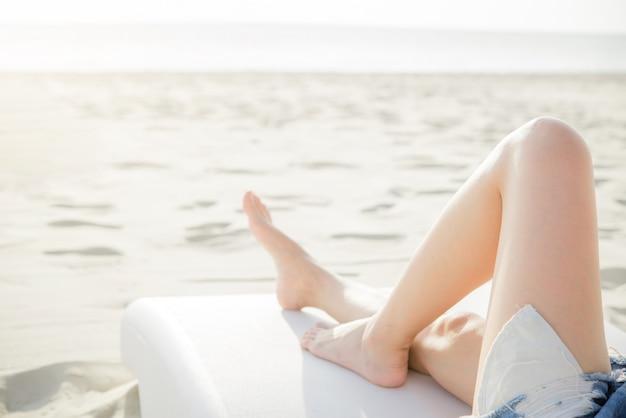 Schöne beine der jungen frau, die auf dem strand stillstehen und sich entspannen Premium Fotos