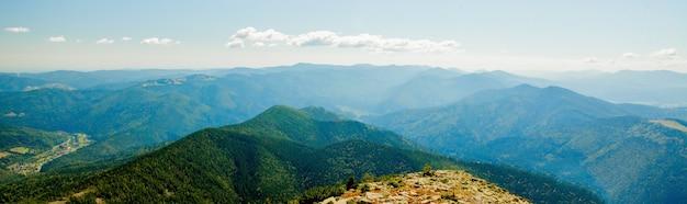 Schöne berglandschaft, wenn die bergspitzen mit wald und einem bewölkten himmel bedeckt sind. Premium Fotos