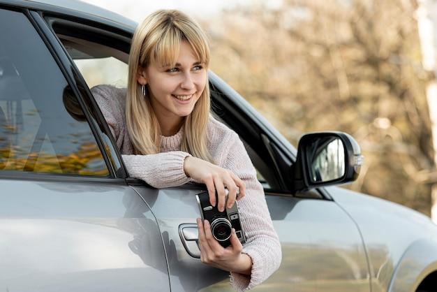 Schöne blonde frau, die eine weinlesekamera anhält Kostenlose Fotos