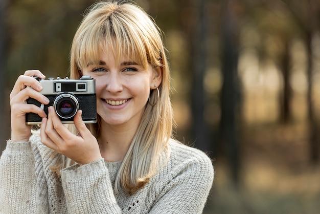 Schöne blonde frau, die eine weinlesekamera verwendet Kostenlose Fotos