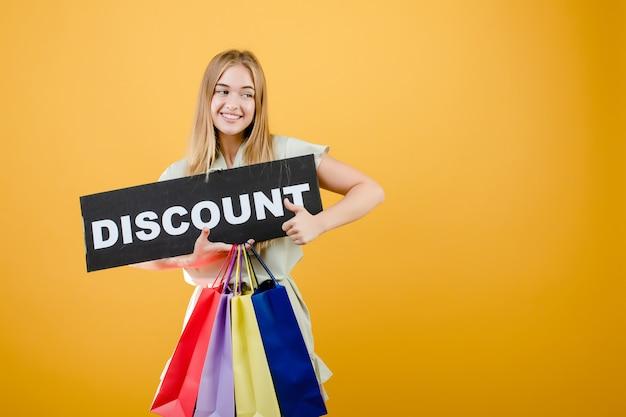 Schöne blonde frau, die mit dem rabattzeichen und bunten einkaufenbeuteln getrennt über gelb lächelt und schreit Premium Fotos