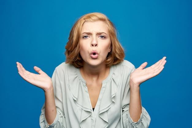 Schöne blonde frau, die mit händen auf blau gestikuliert Premium Fotos