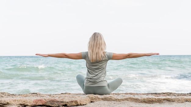 Schöne blonde frau, die yoga am strand tut Premium Fotos