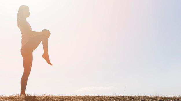 Schöne blonde frau, die yoga im freien tut Kostenlose Fotos
