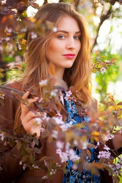 Schöne blonde frau im park an einem warmen frühlingstag Kostenlose Fotos
