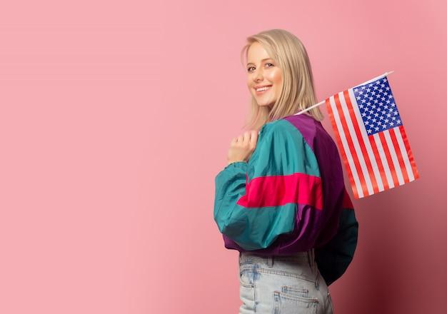 Schöne blonde frau in der kleidung der 90er jahre mit usa-markierungsfahne Premium Fotos