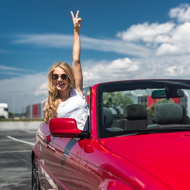 Schöne blonde mädchen in einem umwandelbaren roten auto. sonniger tag Premium Fotos