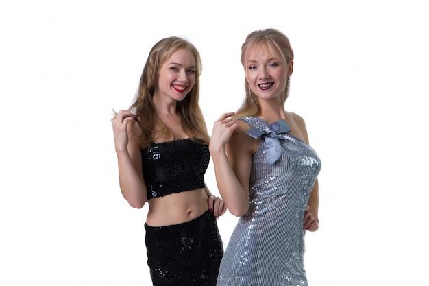 Schöne blonde zwillingsmädchen, die auf einem weiß in den glänzenden kleidern, getrennt aufwerfen Premium Fotos