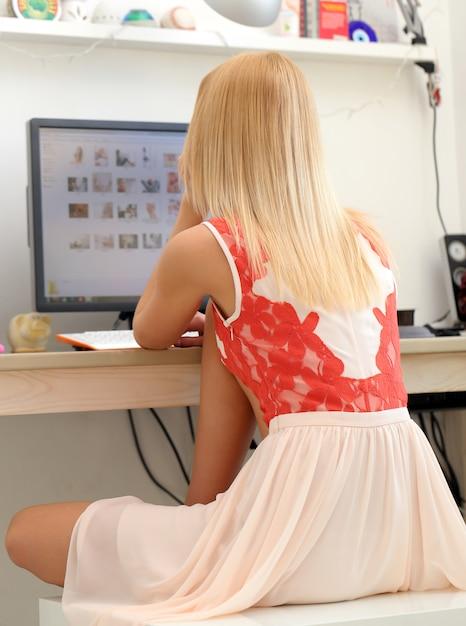 Schöne blondine, die einen computer verwendet Kostenlose Fotos