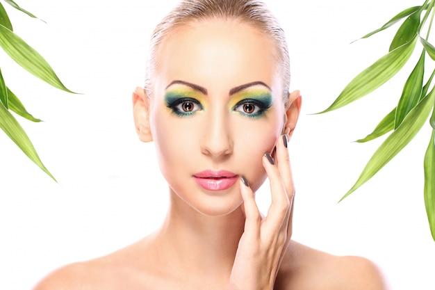Schöne blondine mit bambusblättern Kostenlose Fotos