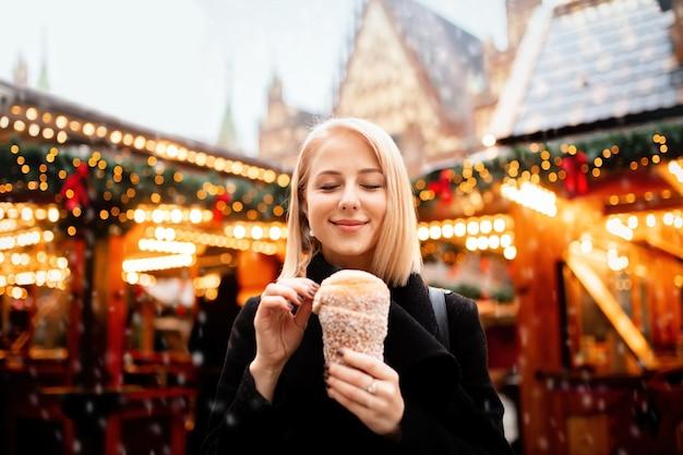 Schöne blondine mit spuckenkuchen am weihnachtsmarkt in breslau, polen Premium Fotos