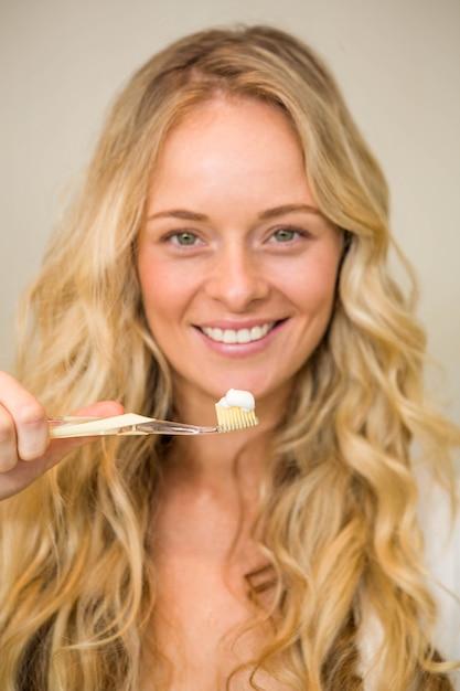 Schöne blondine ungefähr, zum ihrer zähne zu hause zu putzen Premium Fotos