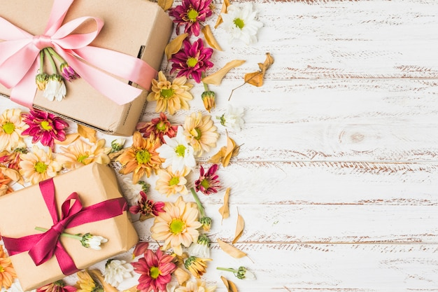 Schöne blumen und eingewickeltes geschenk mit kopienraum für text Kostenlose Fotos