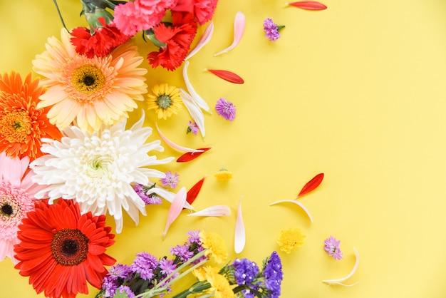 Schöne blumen verzieren auf draufsicht des gelben hintergrundes Premium Fotos