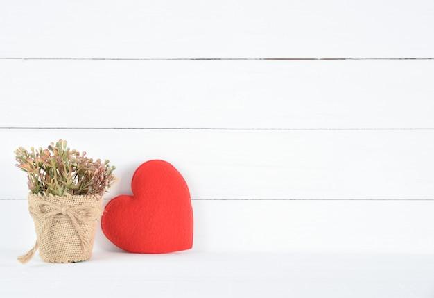 Schöne braune blume in einem topf und in einem roten herzen auf weißem hölzernem hintergrund Premium Fotos