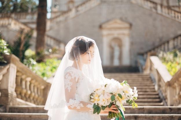Schöne braut bedeckt mit einem schleier mit brautstrauß auf der treppe Premium Fotos