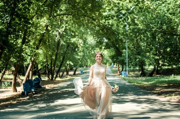 Schöne braut in einem beige kleid mit einem rock-schritt, der in den park geht Premium Fotos